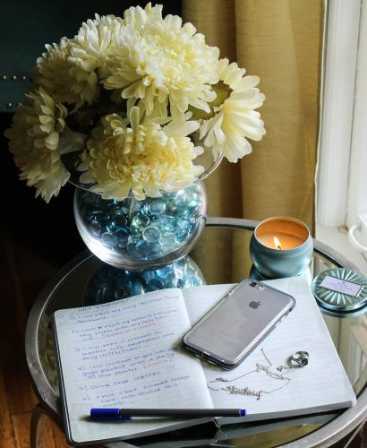 product shot of a journal with an iphone on top, a candle lit and flowers bloom in the background