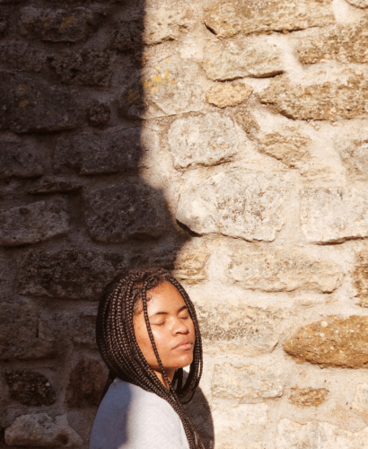image: girl with braided hair who eyes closed in front of a stone wall