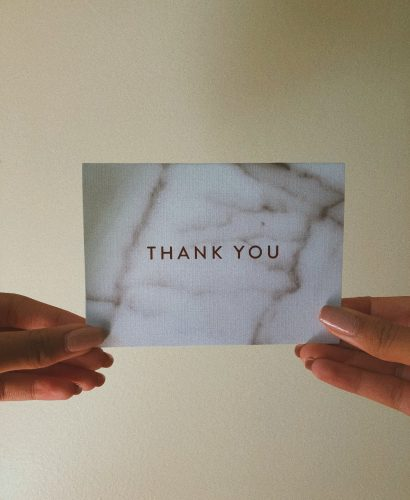 a girl holding a thank you card with both of her hands