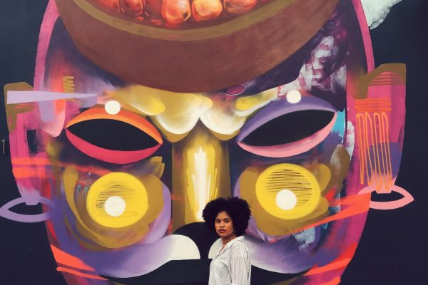 A girl posing in front of a wall mural at Art Basel Miami